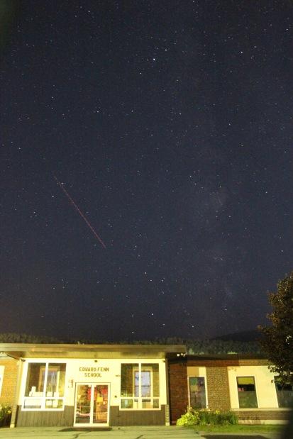 Milky Way (Sagittarius) and path of Boeing 777-300 airliner behind elementary school, Gorham, NH.